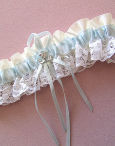 A closeup image showing the Satin and Lace Neptune Garter. This Garter is designed with soft blue and ivory satin ribbons & white lace. The handcrafted thin blue satin ribbon and silver neptune motif setting make an elegant, comfortable & classic garter design. This image shows the motif detailing up close.
