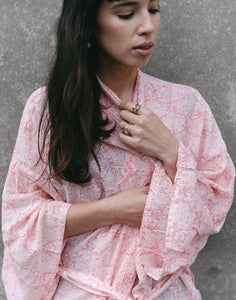 An image of the rosey damask bridal party kimono wedding robe, being worn by a brunette lady. The image shows the flowing kimono sleeves and beautiful drape of the fabric.