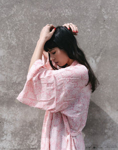 An image of the rosey pink damask bridal party kimono wedding robe, being worn by a brunette lady. The image shows a side on view of the flowing kimono sleeves and beautiful drape of the fabric.