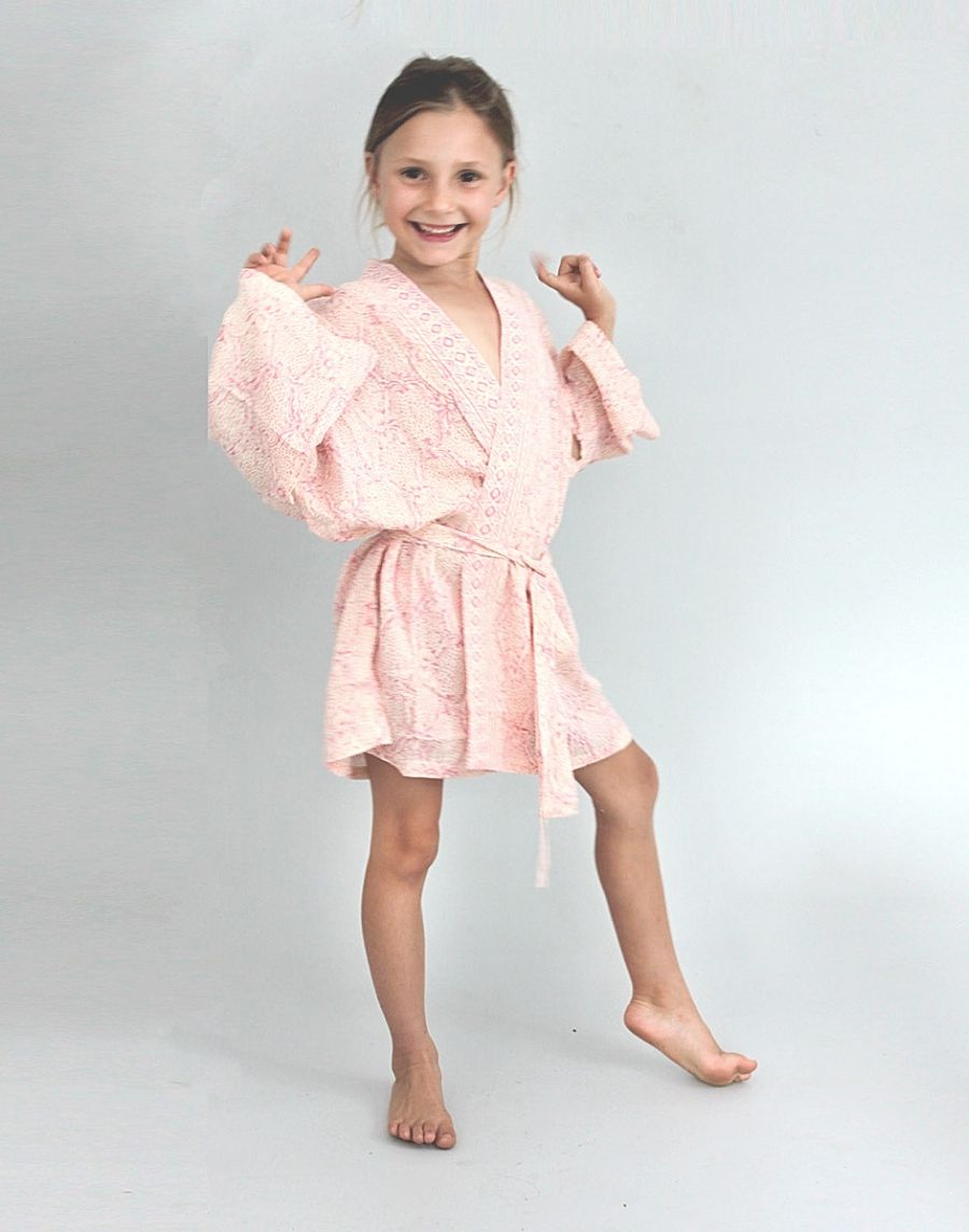 An image of a childs sized flowergirl kimono wedding robe. The rosey pink damask design is pretty and feminine. The image shows the kimono on a young girl and shows the flattering fit.