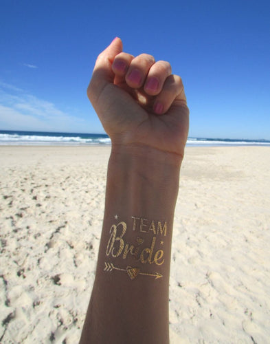 A image of the Team Bride tattoo on a wrist. 'Team' is written in delicate square font & 'Bride' is in a fun designed cursive detailed with love hearts. The Tattoo is underlined with a gorgeous love heart arrow & there are two small stars completing the design. The fun design looks lovely on the wrist & the gold is shimmering in the sunlight.