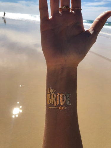 A closeup image of the 'The Bride' tattoo on a wrist. Written in a chunky rounded lovely font with 'the' in lowercase and 'Bride' in large uppercase. The design is completed with a cute arrow underlining the words. The image shows how lovely the Gold colour is on the skin & how it is shimmering in the light.