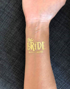 A closeup image of the 'The Bride' tattoo on a wrist. Written in a chunky rounded lovely font with 'the' in lowercase and 'Bride' in large uppercase. The design is completed with a cute arrow underlining the words. The image shows how vivid the Gold colour is on the skin.