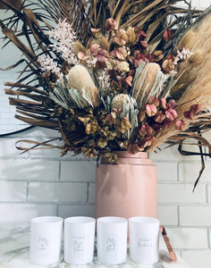 A lifestyle image of the personalised candles. This image shows four beautiful white candle vessels, and the  polished rose gold lid.  The candles are open, and placed on a marble counter, in front of an arrangement of Australian Native flowers. A Polished rose gold candle lid is leaning against the first candle on the right.