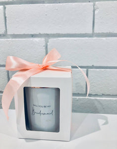 An image of the 'Will you be my bridesmaid' candle. This image shows the beautiful white candle vessel and the polished rose gold lid. The personalised 'Will you be my bridesmaid' text is in a funky elegant cursive text on the front of the candle. The candle is gift packed in a simple white box, with peach bow.