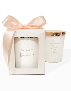 An image of the 'Will you be my Bridesmaid' candle. This image shows the beautiful white candle vessel and the rose gold lid, packaged in a simple white gift box with peach bow.. The personalised text is in a funky elegant cursive text on the front of the candle. Another candle is displayed in the background, showing it out of the gift box.