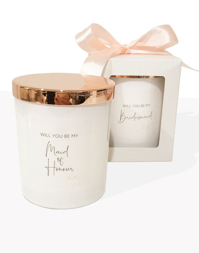 An image of the 'Will you be my Maid of Honour' candle. This image shows the beautiful white candle vessel and the rose gold lid. The personalised text is in a funky elegant cursive text on the front of the candle. Another candle is displayed in the background, showing it packaged in a simple white gift box, with a peach bow.