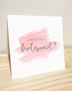 An image of this elegantly designed gift card & envelope.  The white card reads 'Will You Be My Bridesmaid' in whimsical cursive grey text on a pink brushed background. The card is placed above a custom designed white envelope.