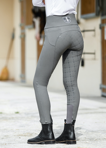 This image pictures a dressage rider in her show attire standing in front of her bay horse. The horse is looking away from the camera while she has turned around and is looking directly into the camera.