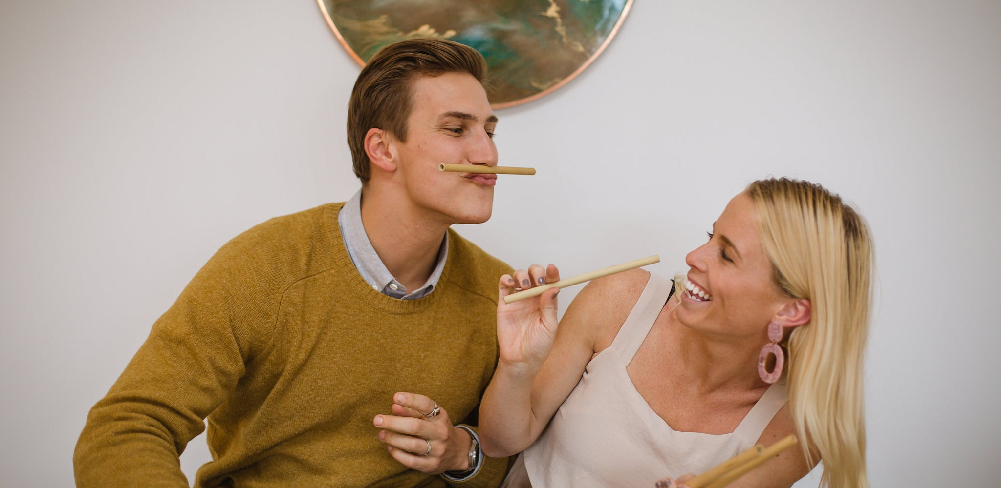 Lennart and Jamie, co founders of theotherstraw, smiling whilst holding bamboo straws
