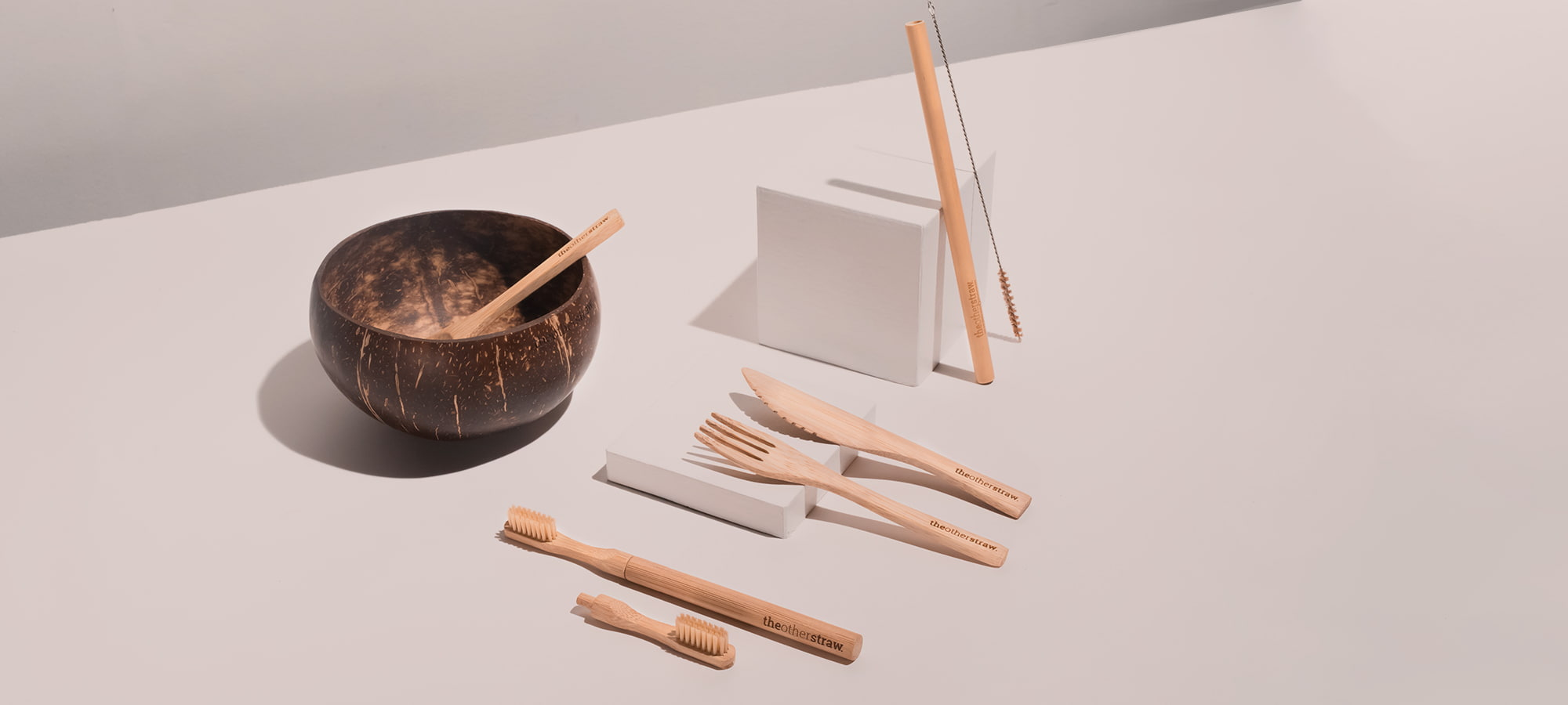 bamboo straw, bamboo cutlery, coconut bowl and bamboo toothbrush on table