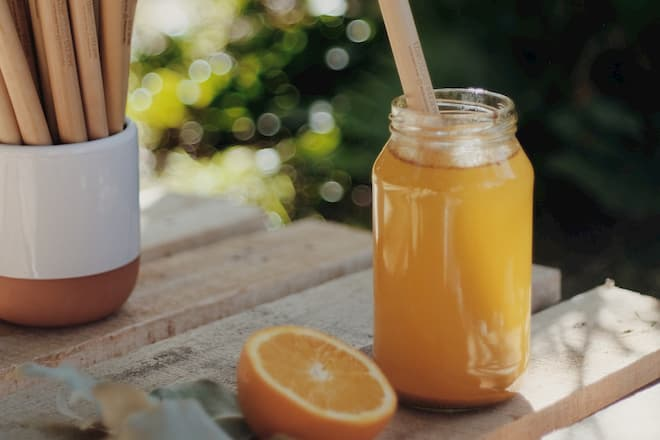 theotherstraw reusable bamboo straw in an orange based juice with reusable straws in the background