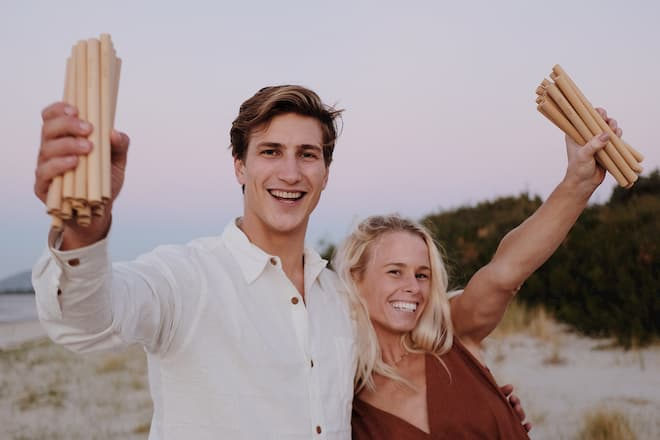photo of Jamie and Len, the co founders of theotherstraw with reusable bamboo straws in their hands