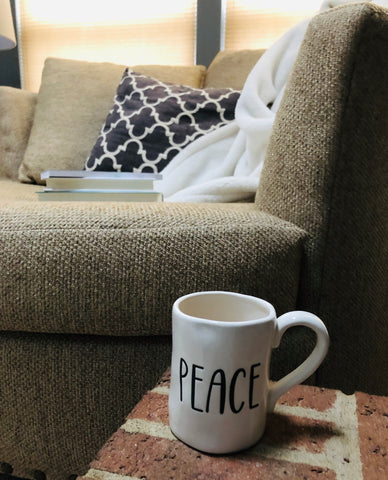 peace mug by chair with books pillows and blanket