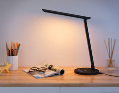 black desk lamp on a desk with the light on, container of pencils and a magazine are on the desk under the light