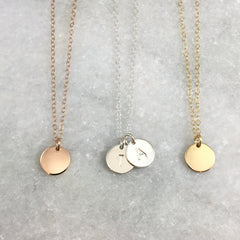 Three small disc necklaces, rose gold, silver with two discs and initials a and t, gold