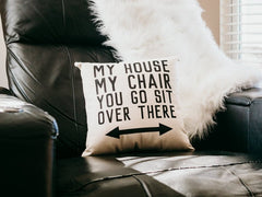 """pillow on black chair, pillow has """"my house my chair you go sit over there"""" in black letters"""