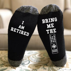 """black socks that say """"I am retired, bring me the remote"""" in white lettering on the bottom"""