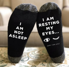 """blue socks that say """"I am not asleep, I am resting my eyes"""" on the bottom in white lettering"""