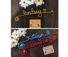 wire bookmarks on wood background, lindsay bookmark with a heart in gold, katelyn bookmark in blue with a turtle charm, brayden bookmark in red with wooden bead
