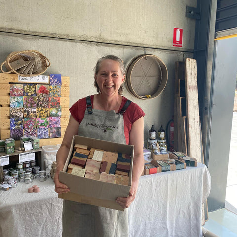 Julie holding our charity soaps. When you buy from us, you support the community