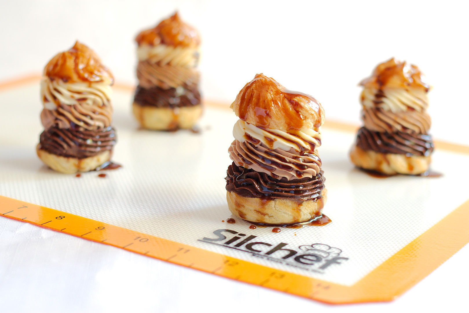 Triple chocolate cream puffs with caramel sauce