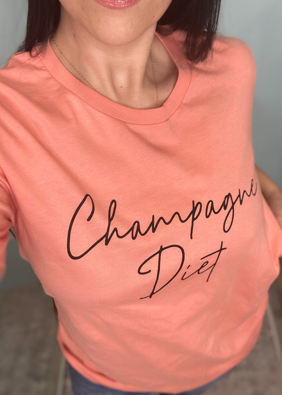 'Champagne Diet' Coral Tee-We're on our Champagne Campaign women's graphic tee! Now this is a diet we can stick to. This tee is bright, fun & a little sassy! Coral Tee Black 'Champagne Diet' in black script on front Solid back Fits true to size - size up for a more oversized look 100% Cotton Machine Wash.-Cali Moon Boutique, Plainville Connecticut