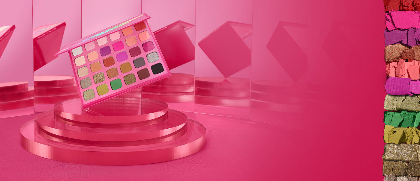 The Jeffree Star Artistry Palette with swatches on a pink and mirror background