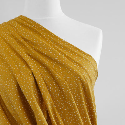 Arizona - Mustard Yellow Ticker Tape, Single Jersey Cotton Elastane Print Fabric Mannequin Close Up Image from Patternsandplains.com