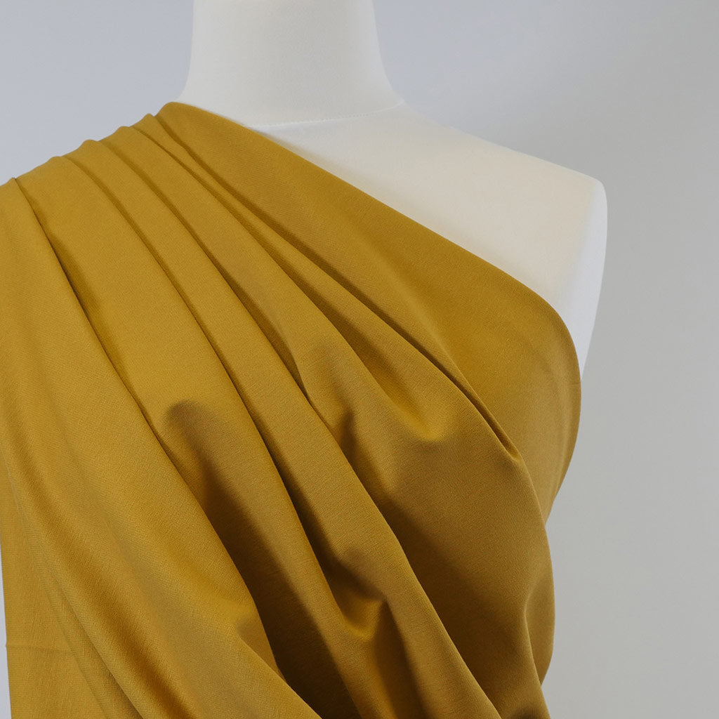 Rome Ochre Yellow Viscose Rich Heavy Ponte de Roma Stretch Fabric Mannequin Closeup Image from Patternsandplains.com