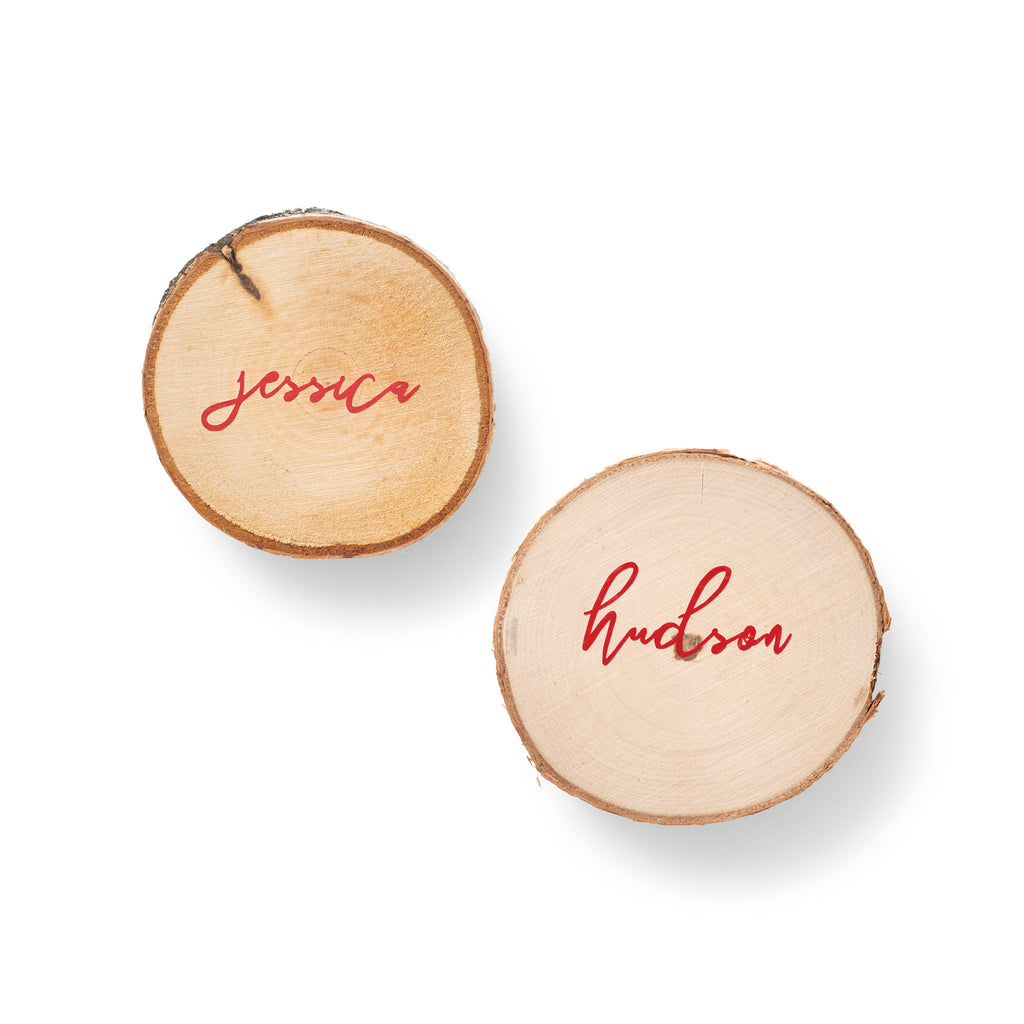 Luxe placecards are custom-painted wood discs.