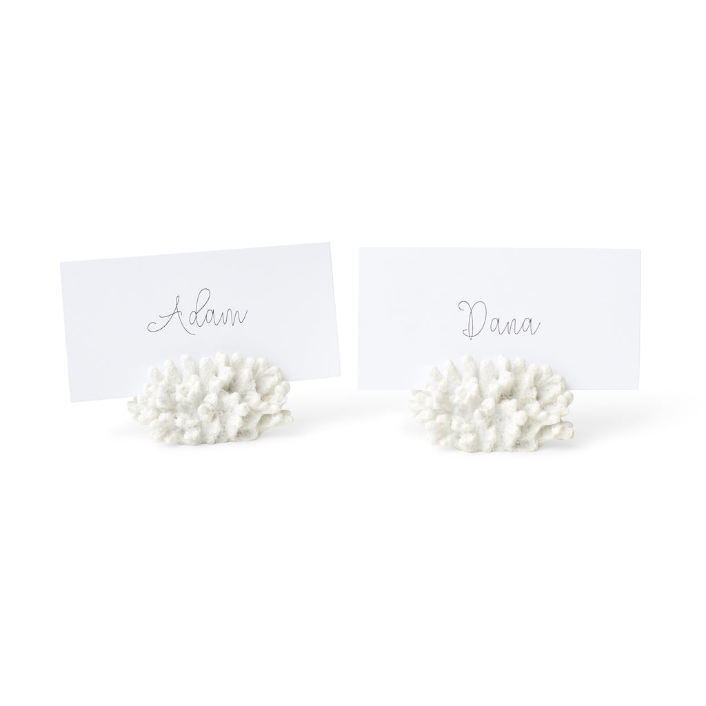 Luxe customized place cards are displayed in faux-coral holders.