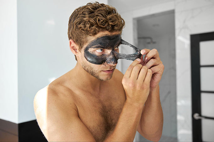 a man peeling off his face mask
