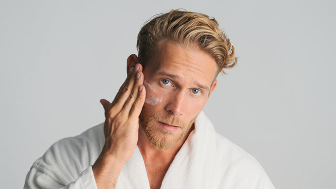 a bearded man in a robe applying moisturizer to his face