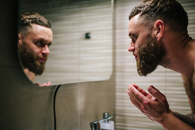 bearded man washing face