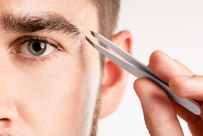 a close-up of a man using tweezers on his eyebrows