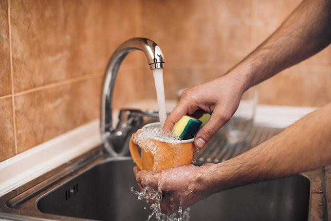 hands and sponge wash a cup