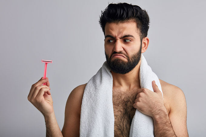 a man holding a razor and looking at it with disgust