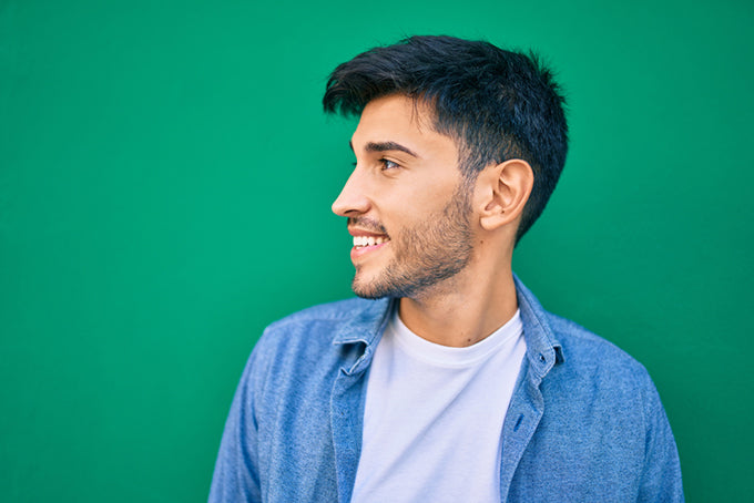 a profile shot of a smiling man against a green background