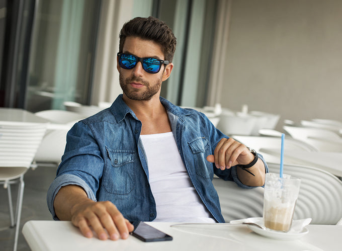 a man with sunglasses sitting at a patio dining table