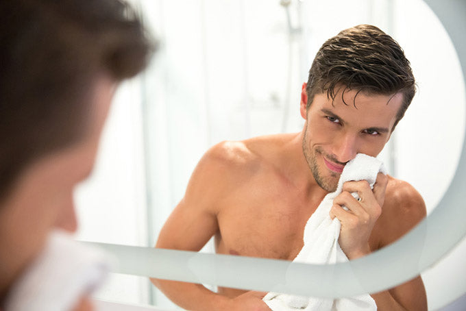 man in towel looking at his reflection