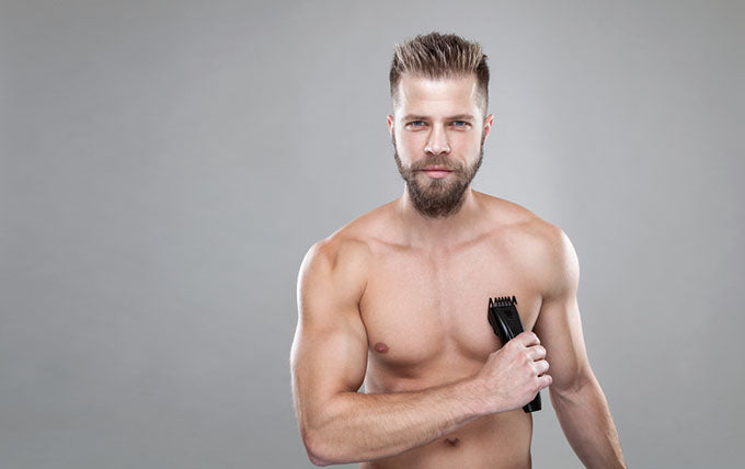 a man using an trimmer on his chest hair