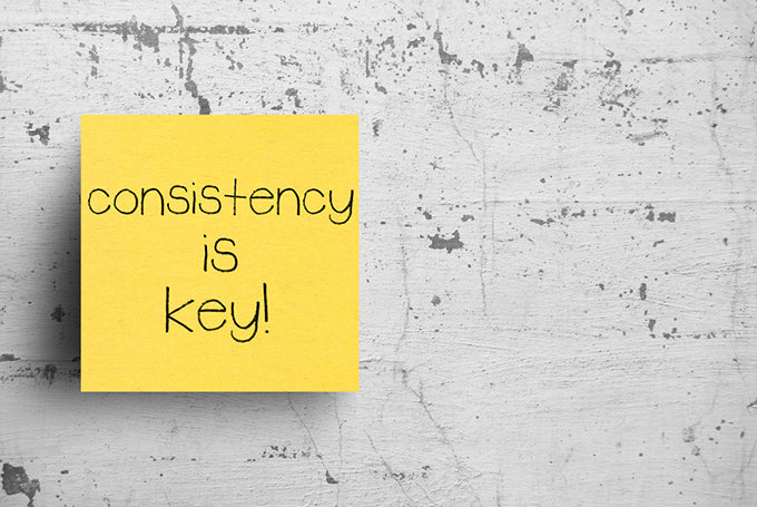 a sticky note on a concrete wall that says consistency is key