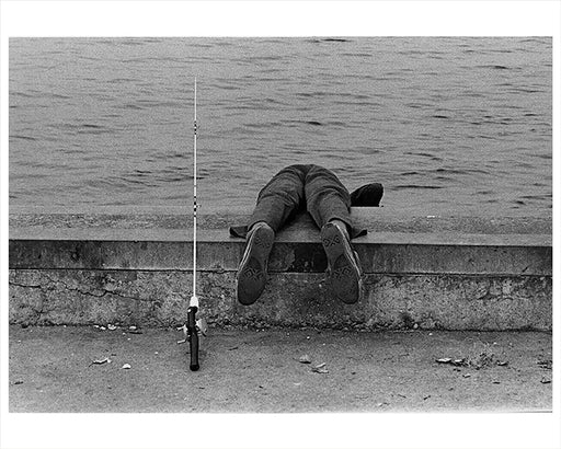 A boy hangs over the edge while fishing at Canarsie Pier, Brooklyn, New York 1972