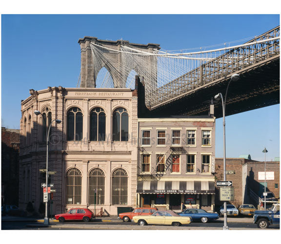 Brooklyn Bridge -  view of Brooklyn Tower emerging behind commercial buildings on the corner of Front Street & Camden Plaza Old Vintage Photos and Images