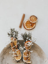 Christmas spirit smudge stick with rosemary, orange slices, and a cinnamon stick bound with natural cotton rope.