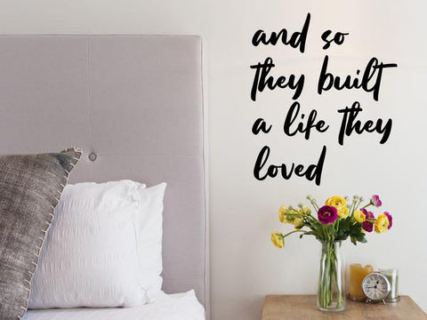Wall decal for bedroom that says 'and so they built a life they loved' on a bedroom wall.