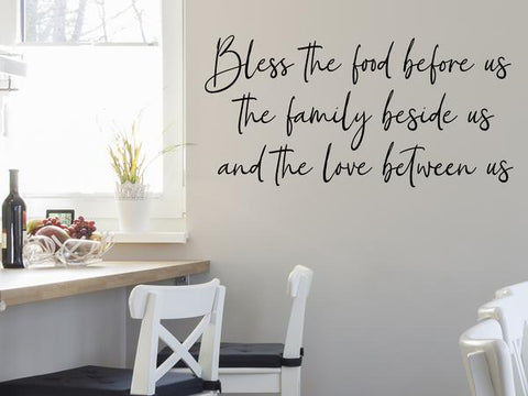 Wall decals for kitchen that say 'BLESS THE FOOD BEFORE US THE FAMILY BESIDE US AND THE LOVE BETWEEN US' on a kitchen wall.
