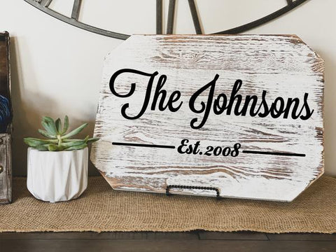 Custom home wood signs that says, 'The Johnsons' placed on a wood table.