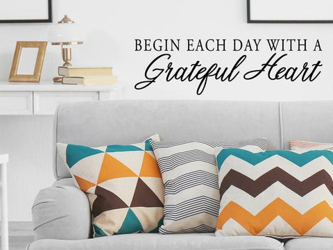 Living room wall decals that say 'Begin each day with a grateful heart' on a living room wall.